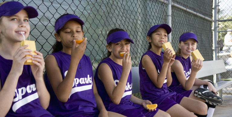 Little league players drinking juice boxes and eating snacks